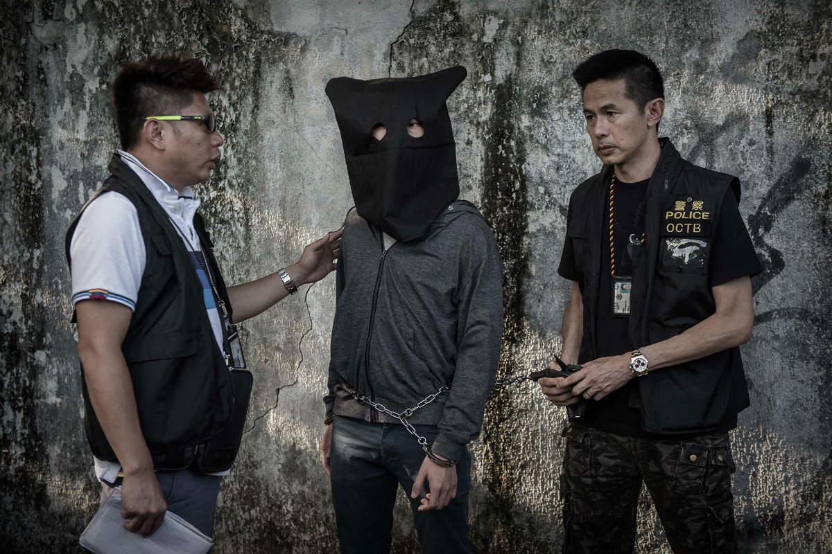Полиция Гонконга сопровождает подозреваемого во время реконструкции преступления в районе Сайкун, на следующий день после обнаружения взрывчатых средств в заброшенной телестудии. Инцидент случился накануне голосования по ряду спорных вопросов относительно изменений в Конституции