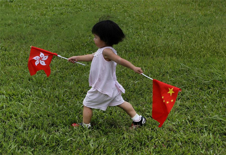 Девочка с флагами Гонконга и КНР на дне открытия военной базы НОАК в Гонконге.