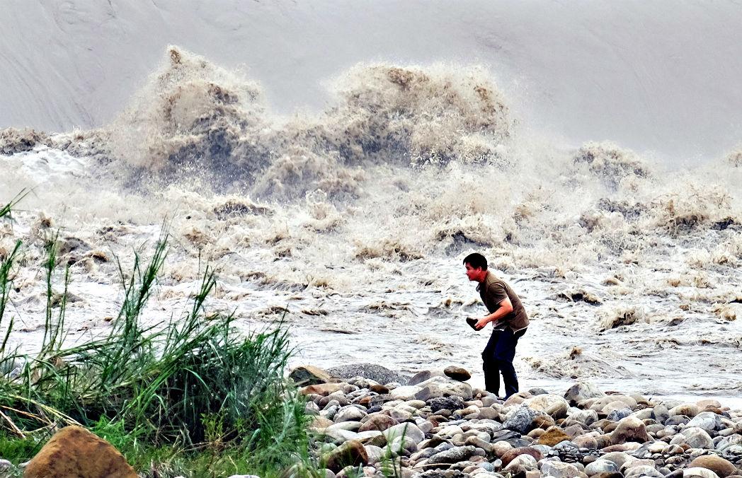 Житель Тайваня собирает камни на реке Синьдянь после прихода мощного тайфуна Ду-Цюань 29 сентября.