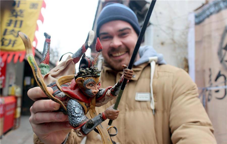 Турист радуется покупке фигурки Царя Обезьян, сделанной народным ремесленником в Сучжоу.