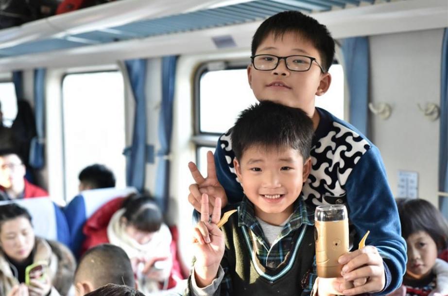 Пассажиры поезда Гуанчжоу—Чэнду, девятилетний Ван Цзяхуэй и шестилетний Ван Цзяжуй показывают электробритву, которую везут в подарок дедушке на китайский Новый год .