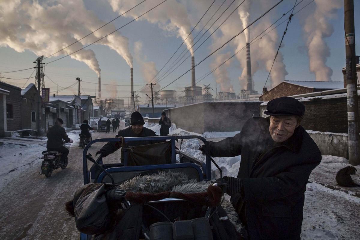 Рабочие толкают тележку на фоне работающей угольной электростанции в провинции Шаньси. Этот снимок выиграл первый приз в номинации «Повседневная жизнь/одиночное фото» на World Press Photo Awards.