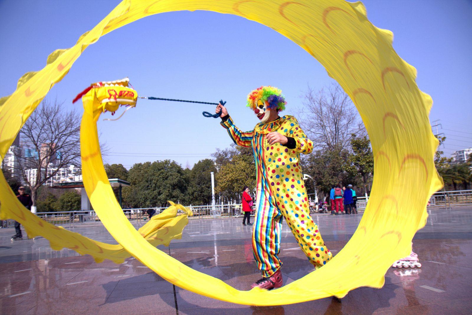 Клоун на роликовых коньках играет с тряпичным драконом в городе Ухань.