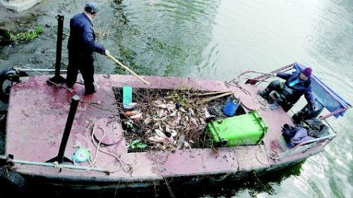 Сотрудники парка Даминху вычищают мертвую рыбу из озера. Фото: en.people.cn