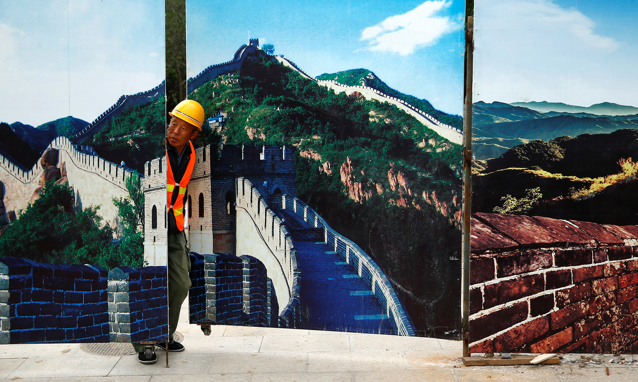 Строитель на фоне забора, декорированного под китайскую стену, Пекин. Фото: REUTERS/Thomas Peter