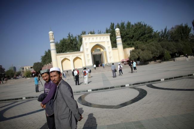 Мусульмане-уйгуры на фоне мечети в городе Кашгар, СУАР. Фото: Reuters