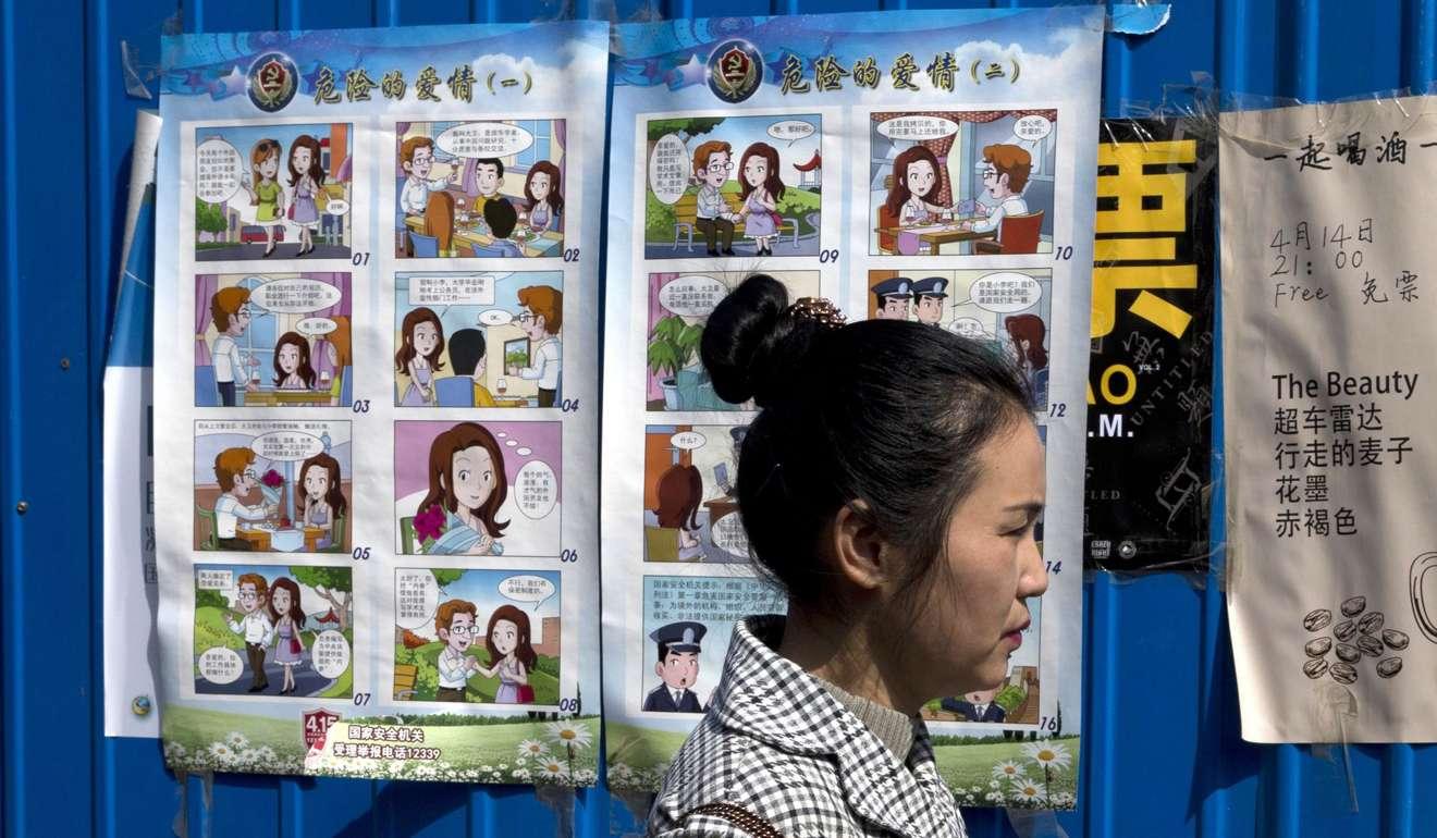 Девушка на фоне плакатов, призывающих к осторожности при общении с иностранцами. Фото: AP