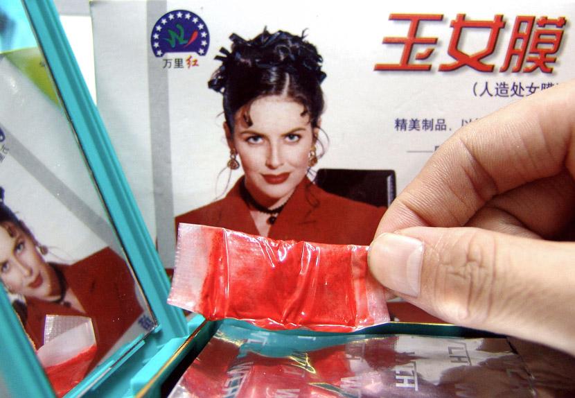 Образец искусственной девственной плевы на витрина магазина в Чжэнчжоу, провинция Хэнань, 14 июня 2004. Фото: Sha Lang/VCG