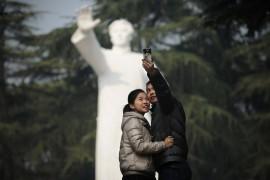 """Молодая пара фотографируется на фоне статуи Мао Цзэдуна в его родном городе Шаошань провинции Хунань. Тысячи людей посетили Шаошань, чтобы почтить память """"великого кормчего"""""""