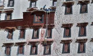 Рабочие красят стены дворца Потала в Лхасе, Тибет.