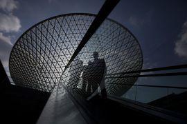 Люди на эскалаторе на фоне Expo Axis в Шанхае, крупнейшей в мире мембранной крыши.
