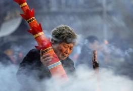 Женщина в буддийском храме в городе Хуайань, провинция Цзянсу. Китай отмечает праздник Лаба, который в этом году выпал на 28 января. Это своеобразная прелюдия ко встрече китайского Нового года.