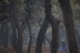 Буддист в маске от смога медитирует в парке Храма Неба, Пекин.